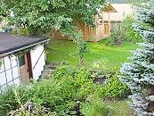Blick auf den kleinen Gartenteich und Garage